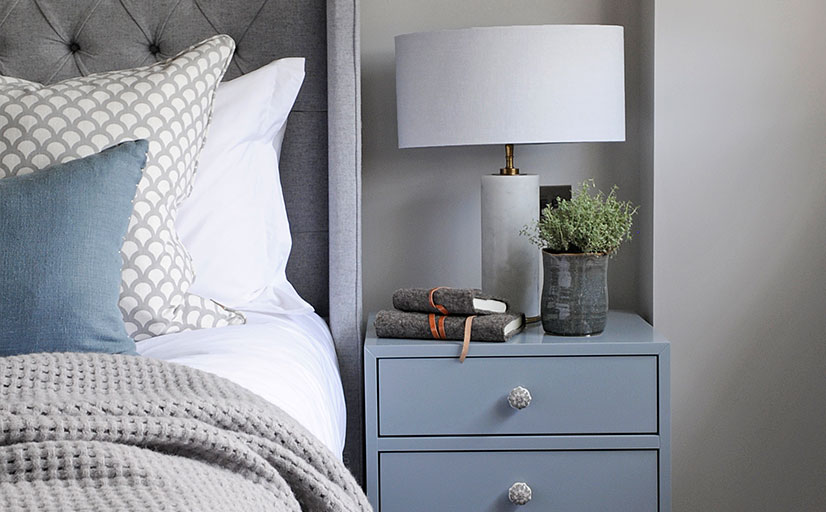 master bedroom with winged headboard and light blue bedside table